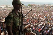A soldier from the M23 rebel group looks on as thousands of Congolese people listen during an M23 rally, in Goma, eastern Congo, Wednesday, Nov. 21, 2012. Thousands of Congolese soldiers and policemen defected